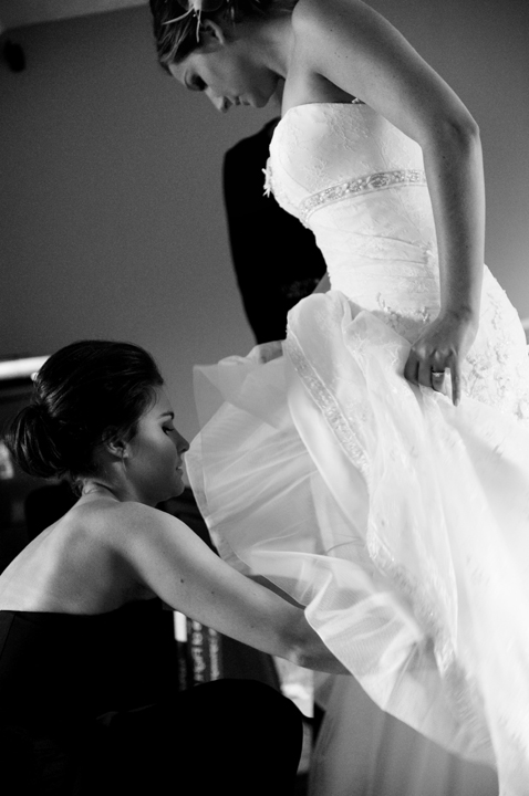 Bride putting on her wedding gown by her maid of honor