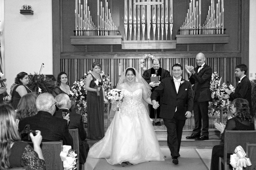 The bride and groom were beaming as they walked down the aisle.